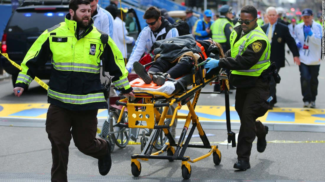 A victim of the explosions is wheeled across the finish line by first responders.