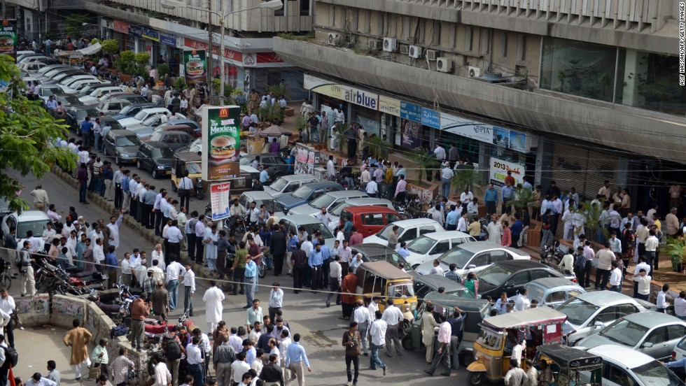 People stand outside after evacuating buildings following tremors in Karachi.