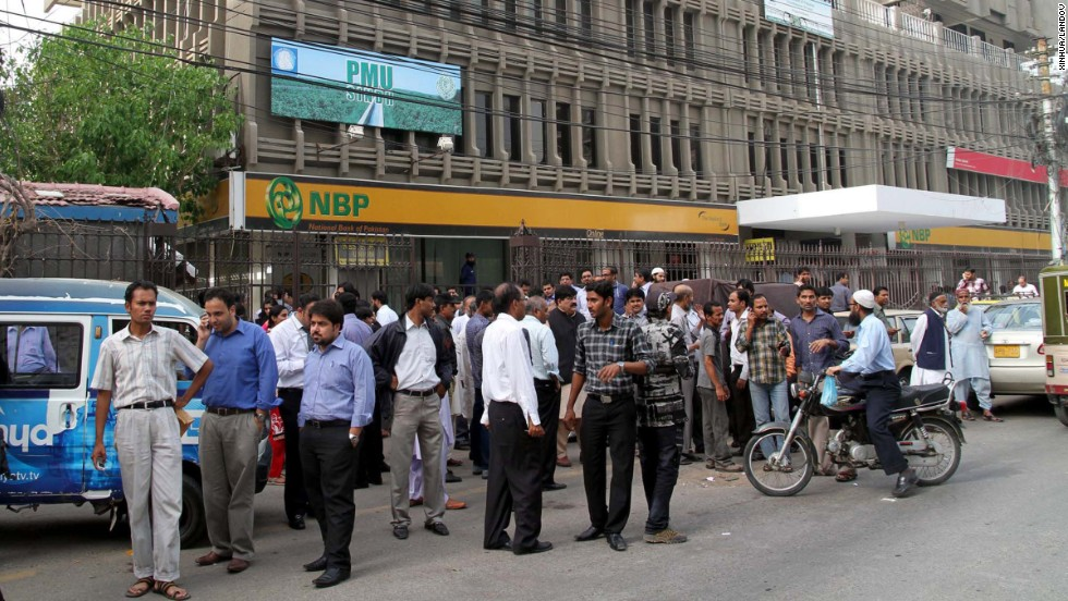 People stand outside in Karachi after the quake on Tuesday.