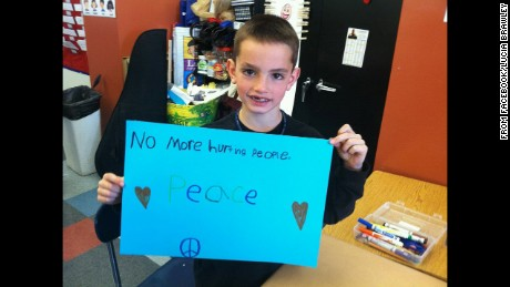 An image taken from Facebook shows bombing victim Martin Richard, 8, holding a sign created for a 2012 peace walk.