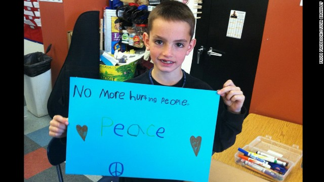 """An image taken from Facebook shows Martin Richard, the 8-year-old killed during the explostions at the Boston Marathon, holding a shign calling for peace.  The sign was created for a """"peace walk"""" that Richard and his fellow second graders took part in in 2012."""