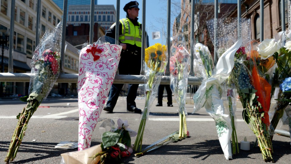 Flowers rest against a police barricade down the street from the Boston Marathon's finish line on April 16.
