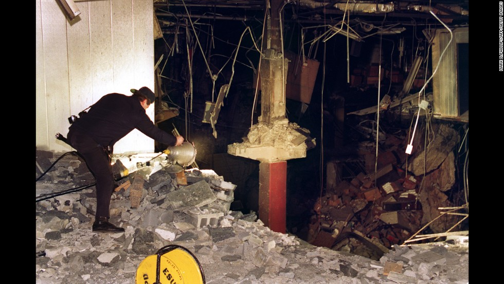 A police photographer helps document the bombing of the underground parking garage at the World Trade Center. That bombing killed six people on February 26, 1993. Six suspects were convicted of participating in the bombing. The seventh suspect, Abdul Rahman Yasin, is still at large. Ramzi Yousef directed the organization and execution of the bombing. He said he did it to avenge the sufferings Palestinian people had endured at the hands of U.S.-aided Israel.