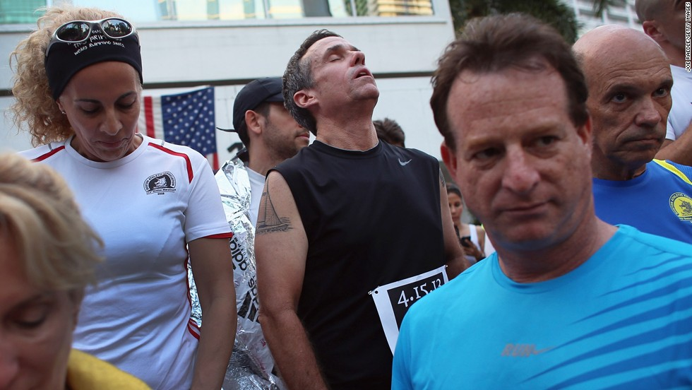 Five-time Boston Marathon runner Jose Sotolongo, center, reacts during a moment of silence in Miami on April 16, 2013.