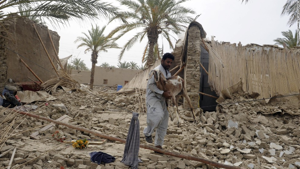 An earthquake survivor carries a goat through the rubble in Mashkell on Wednesday.