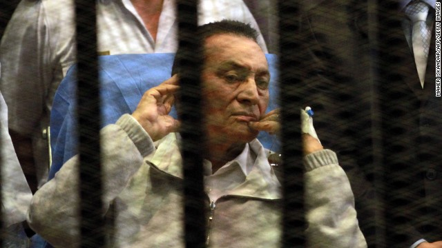 Ousted Egyptian president Hosni Mubarak sits behind bars during his retrial at the Police Academy in Cairo on April 15, 2013.