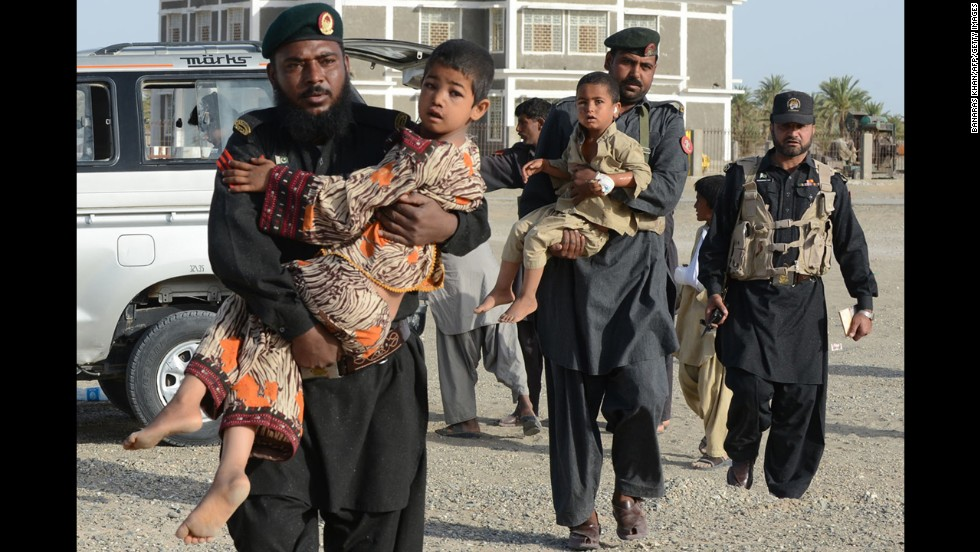 Pakistani Frontier Constables carry survivors toward an army helicopter in Mashkell on Thursday.