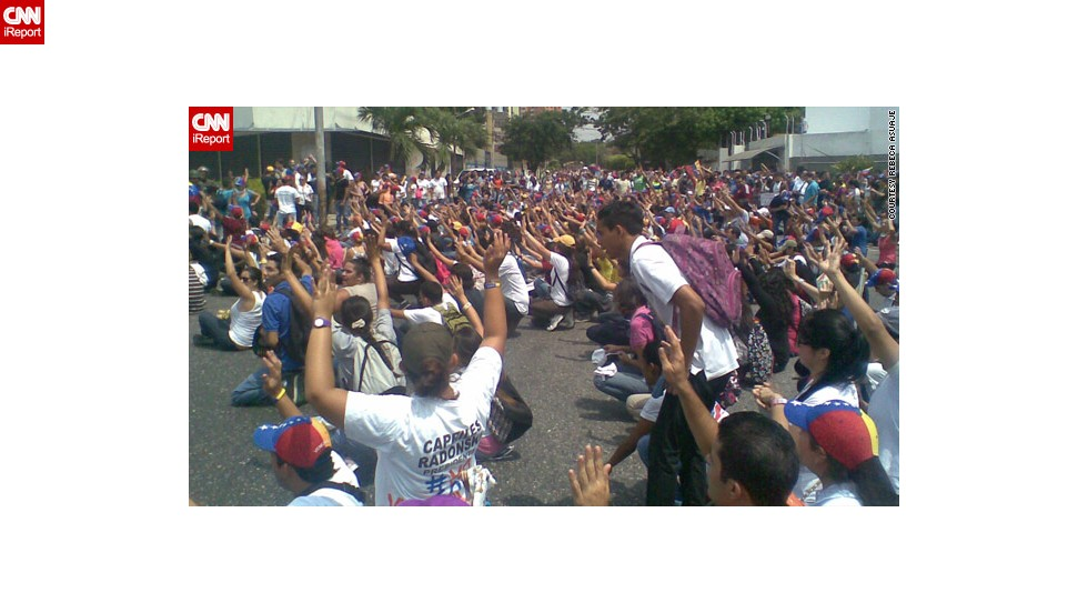 "Also in Barquisimeto, medical student <a href=""http://ireport.cnn.com/docs/DOC-958057"">Rebeca Asuaje</a> captured this image of opposition protesters raising their arms to dispute the results."