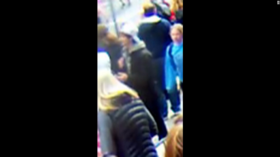 Suspect 2 walks through the crowd.