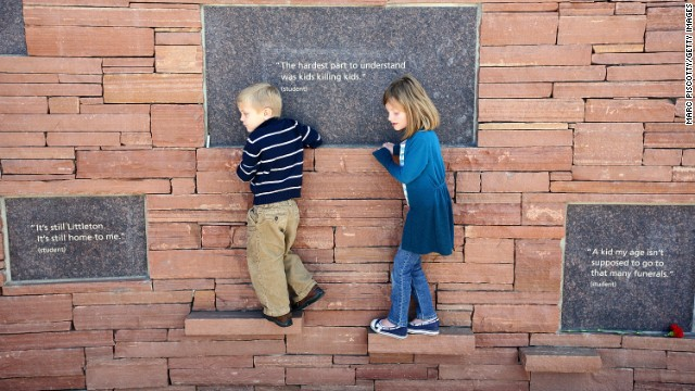 Children, a sister and  brother, walk along the Columbine Memorial at the Columbine Memorial Park in Littleton, Colorado.