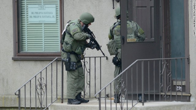 Image #: 22042185    epa03668210 SWAT officers go to a door with guns ready as they search neighborhoods yard by yard after a police chase and shootout with two heavily armed men shortly following the shooting of an MIT police officer just three days after the dual bombings at the Boston Marathon in Watertown, Massachusetts, USA, 19 April 2013. Three people were killed and over 100 were injured when two bombs exploded on 15 April 2013 at the finish line of the marathon. The two suspects in the Boston Marathon bombings are brothers, aged 19 and 20, NBC News reported. Law enforcement officials told the broadcaster that the men, one of whom has been killed in a shootout with police, are of Chechen origin and have permanent resident status in the United States.  EPA/MATT CAMPBELL /LANDOV