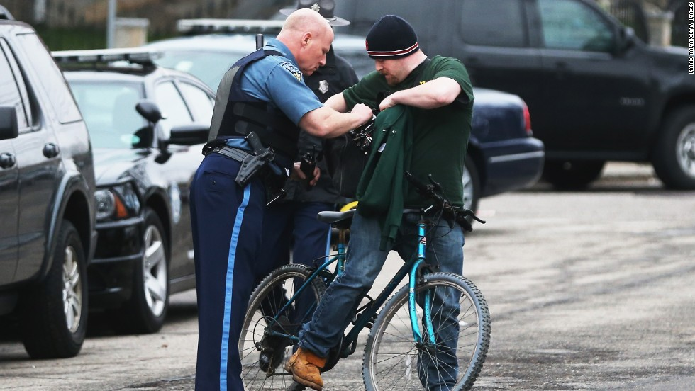 A Massachusetts State Police officer checks the bag of a cyclist amid heightened security on Friday in Watertown.