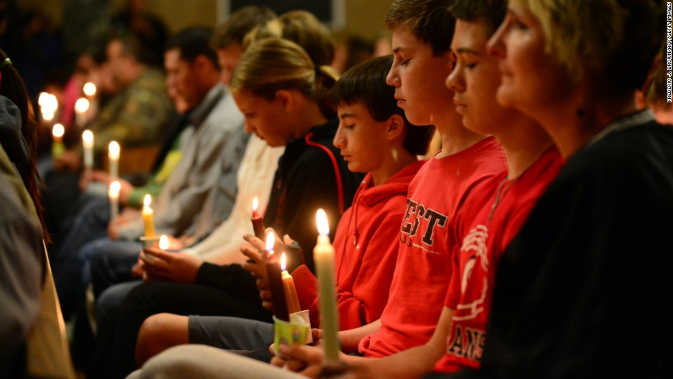 People gather for a candlelight vigil at a church in West on April 18.