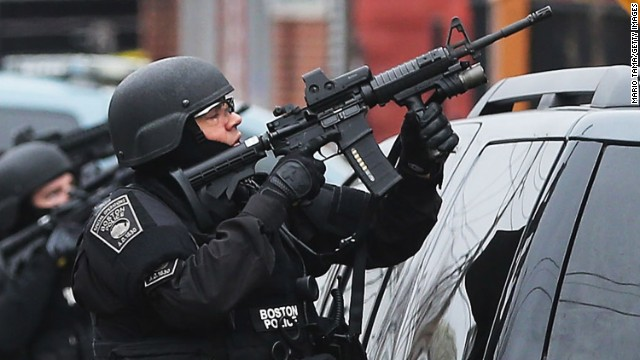 WATERTOWN, MA - APRIL 19: A Boston SWAT team member takes up as posistion as they search for 19-year-old bombing suspect Dzhokhar A. Tsarnaev on April 19, 2013 in Watertown, Massachusetts. After a car chase and shoot out with police, one suspect in the Boston Marathon bombing, Tamerlan Tsarnaev, 26, was shot and killed by police early morning April 19, and a manhunt is underway for his brother and second suspect, 19-year-old suspect Dzhokhar A. Tsarnaev. The two men, reportedly Chechen of origin, are suspects in the bombings at the Boston Marathon on April 15, that killed three people and wounded at least 170. (Photo by Mario Tama/Getty Images)