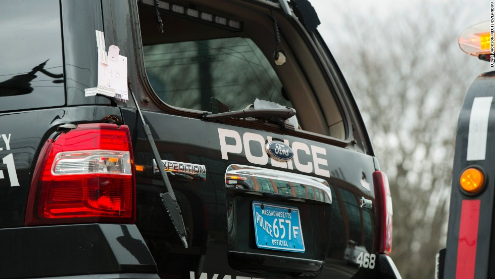 A Watertown police vehicle with bullet holes in its body and a shattered windshield is towed out of the search area on April 19 in Watertown, Massachusetts.