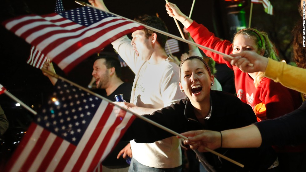 People wave U.S. flags as police drive down the street on April 19.