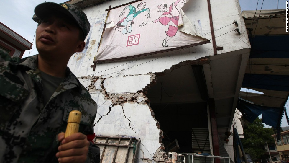 A rescuer stands by a damaged building in Longmen on Saturday.