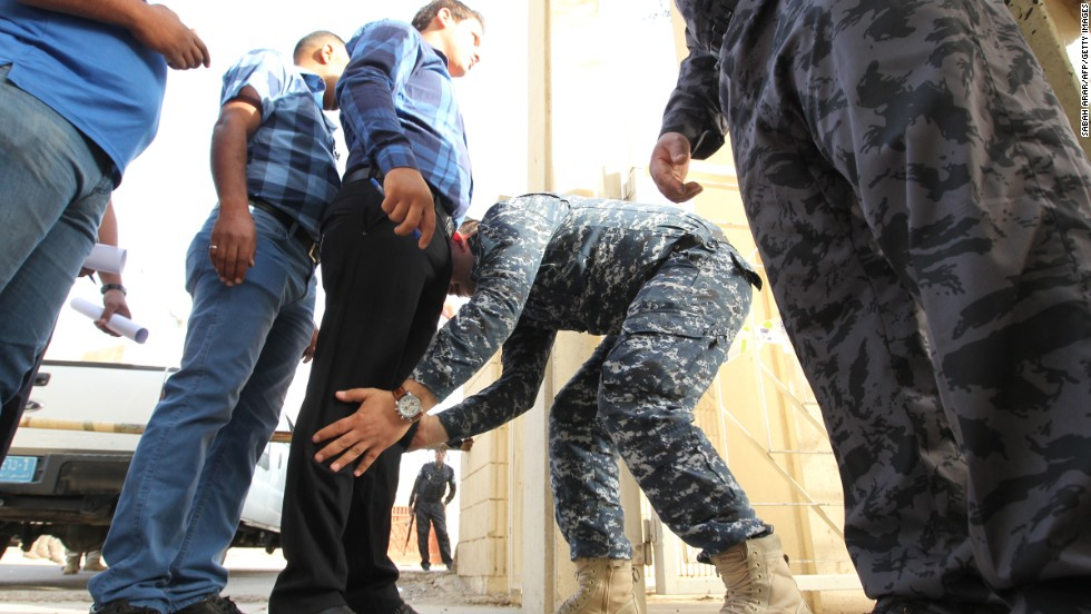 Iraqi security forces frisk men arriving to cast their votes on Saturday.