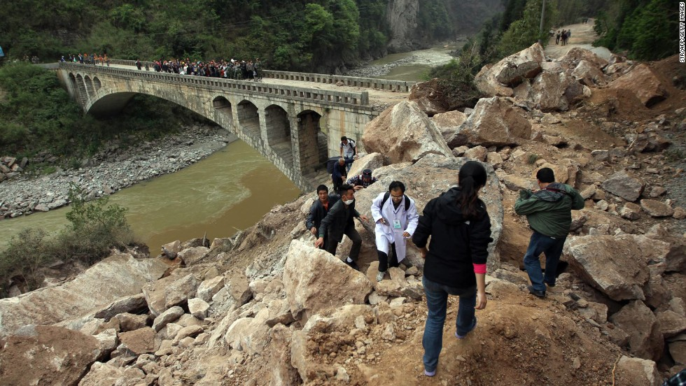 Survivors and rescuers make their way along a damaged area in Lushan on Sunday.