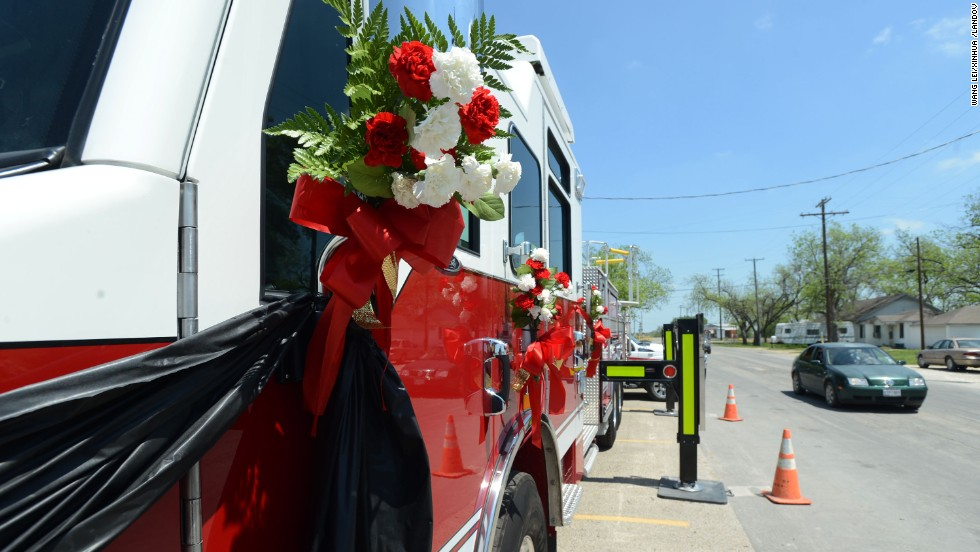 Flowers are tied on a firetruck on April 22 as a memorial for the firemen who died while responding to the explosion.