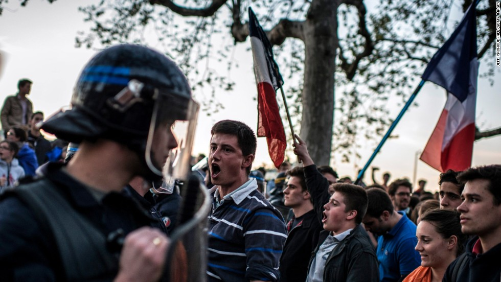 Opponents of same-sex marriage shout slogans and wave French national flags in Lyon on April 23.