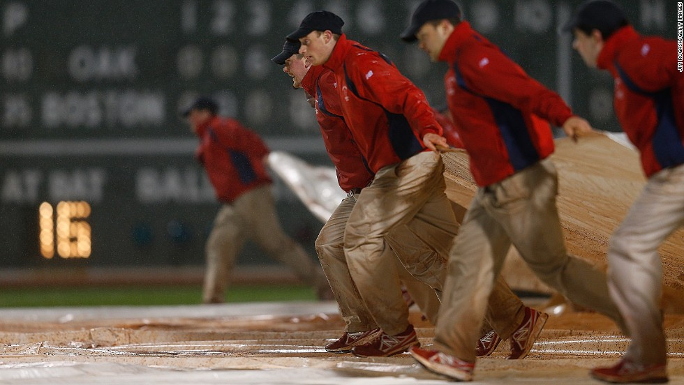 The grounds crew covers the field at Fenway Park in the eighth inning because of rain during a game between the Oakland Athletics and the Boston Red Sox on Tuesday, April 23, in Boston.