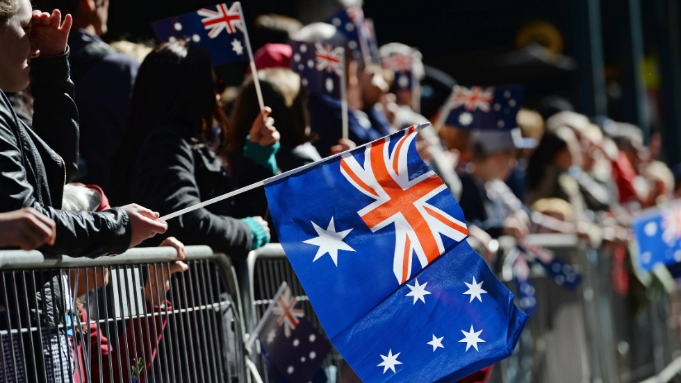 Spectators wave flags as they watch the ANZAC Day parade through Sydney on Thursday. Tens of thousands of Australians and New Zealanders turned out  to honor their war dead, with moving tributes to fallen friends and calls to not forget those injured in conflict.