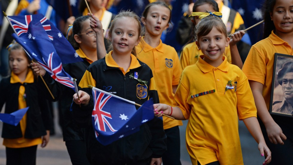 Young children wave flags as they participate in the ANZAC Day march in Sydney on Thursday.