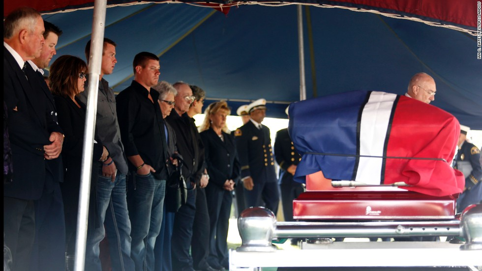Family and friends stand in front of Harris' casket at the cemetery on April 24.