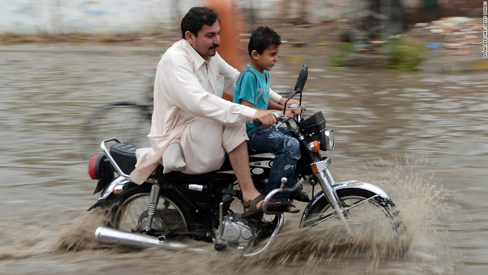 A Pakistani motorcyclist crosses a flooded street after heavy rain in Peshawar on April 26. Pakistan has suffered devastating monsoon floods for the last three years, including the worst in its history in 2010, when catastrophic inundations killed almost 1,800 people and affected 21 million.