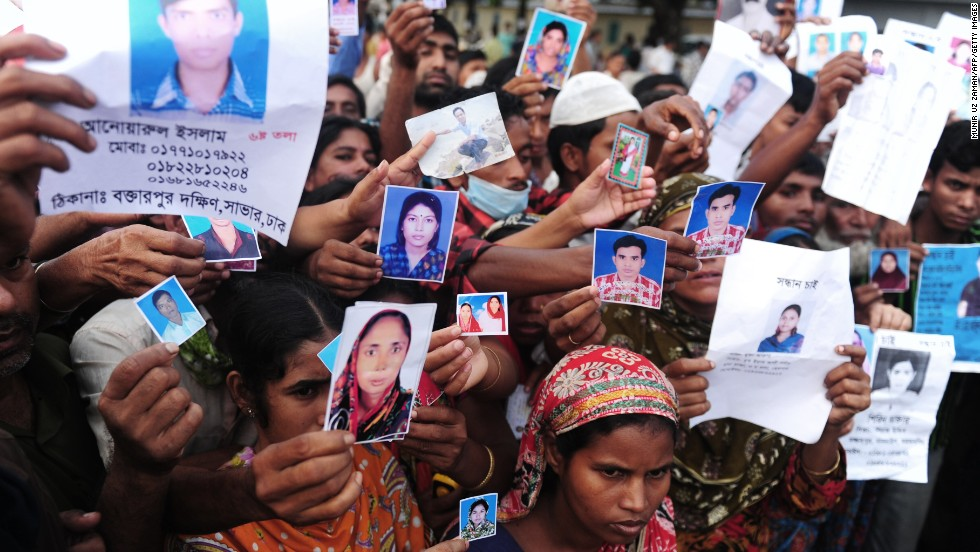Relatives hold photos of missing and dead workers outside the factory April 27.