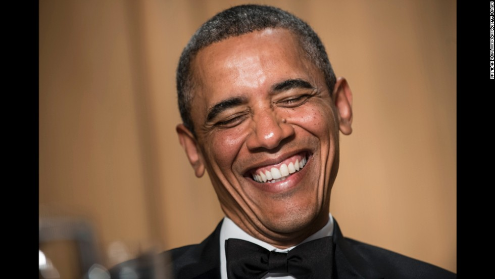 Obama laughs at the comments made during the dinner.
