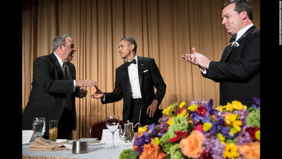 Fox News Vice President Michael Clemente shakes Obama's hand as Fox News correspondent Ed Henry watches.