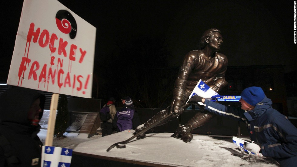 A protester places a Quebec flag on a statue of former NHL hockey player Guy Lafleur in Montreal. While Quebecers don't participate in hockey en masse the way they used to, it's still the most popular sport there.