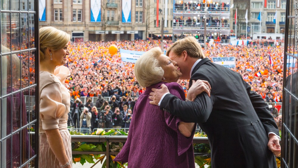 Princess Beatrix of the Netherlands kisses her son, the now King Willem-Alexander as the now Queen Maxima looks on during a short address to the public after Queen Beatrix abdicated ahead of the investiture of Willem-Alexander on Tuesday, April 30, in Amsterdam, in this image provided by Netherlands Government Information Service.