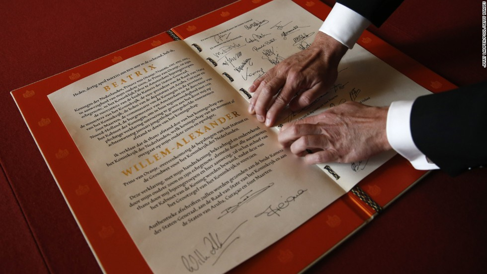A man displays the Act of Abdication signed by Princess Beatrix, her son King Willem-Alexander and his wife Queen Maxima during the abdication ceremony.