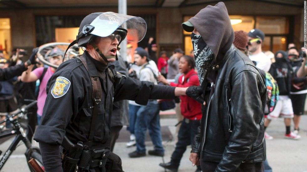 A police officer and demonstrator clash during May Day demonstrations in Seattle on Wednesday, May 1. A peaceful protest turned violent, and police say they sprayed demonstrators with pepper spray after they threw everything from metal pipes to fireworks at officers. Hundreds of thousands of people across the globe take to the streets on May 1 to demand better working conditions during what is known as International Workers' Day.