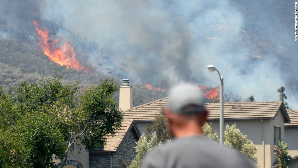 A resident watches as a wildfire approaches homes in Newbury Park.