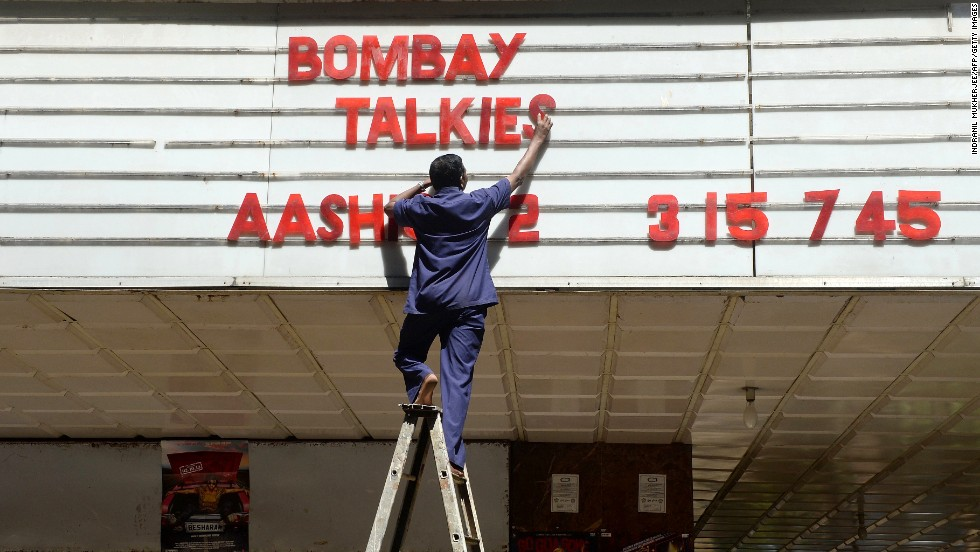 "An employee of the New Excelsior Theatre in Mumbai puts up letters promoting the new anthology ""Bombay Talkies"" on May 3. The film's release coincides with the celebration of 100 years of cinema in India."