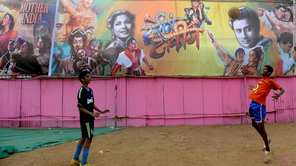 Yong men play in front of a collage of various Indian movies at a field in central Mumbai on April 19.