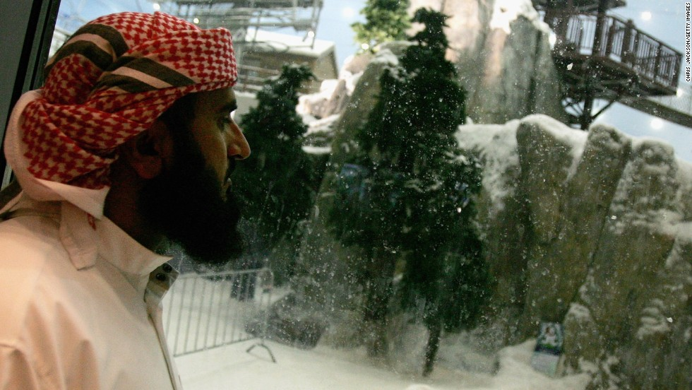 A gentleman wearing a traditional Emiratian dishdasha looks through a glass window at the Ski Dubai snowdome at Mall of the Emirates. The snowdome is billed as the world's largest.