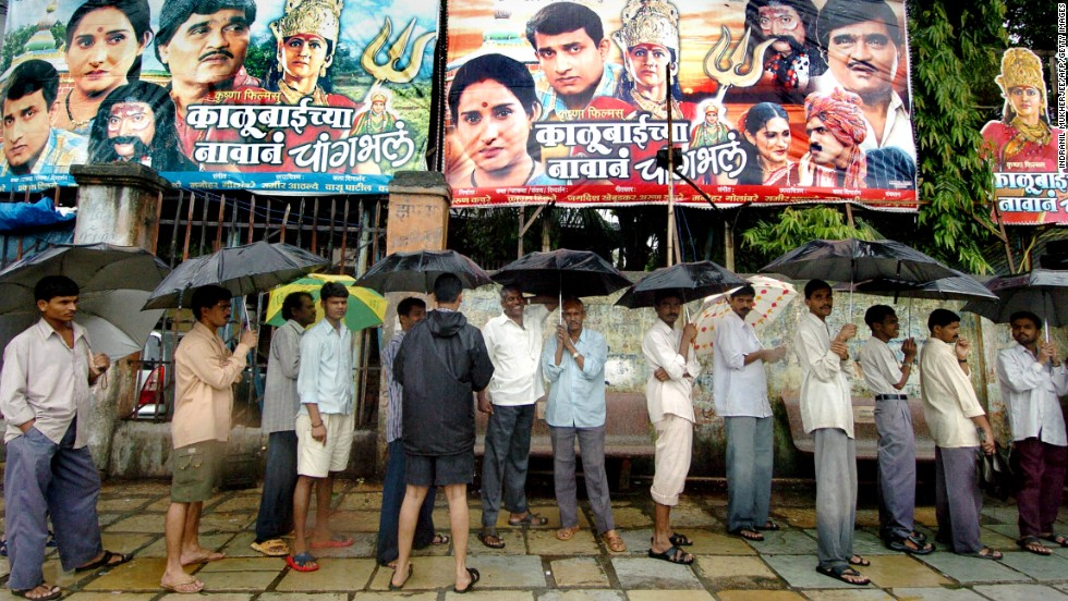 Indian cinema enthusiasts queue up in the rain outside a theater in Mumbai on August 1, 2005.