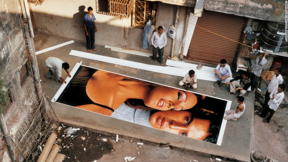 Men stand around the courtyard of a cinema billboard printing house in Mumbai in 2002. Billboards are printed in several sections and then reassembled as one massive image.