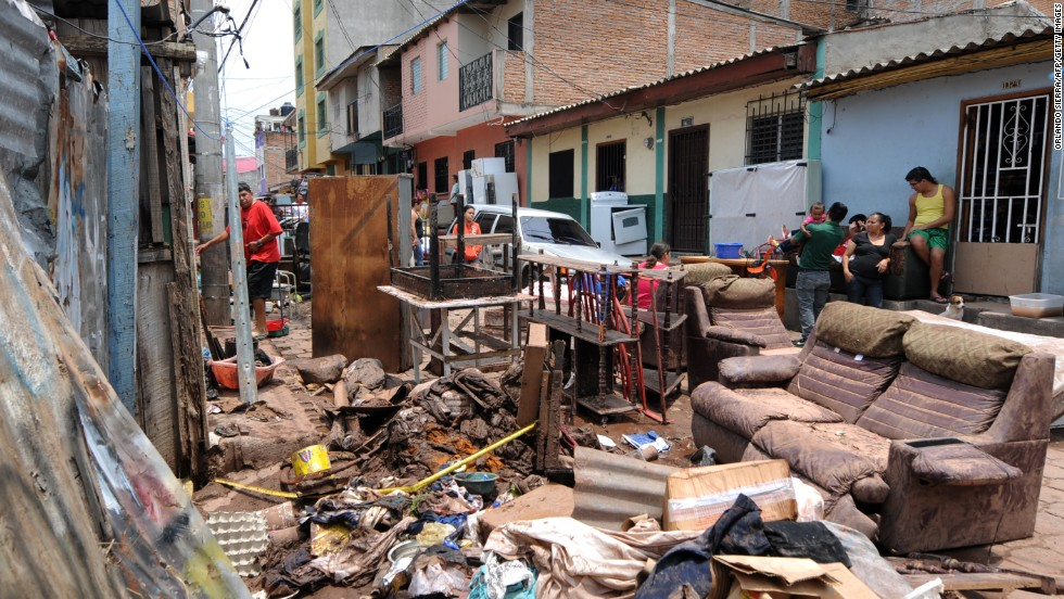 People in the Morazan neighborhood of Tegucigalpa, Honduras, sort through the remains of their possessions after heavy rains left two people missing and destroyed streets and homes.