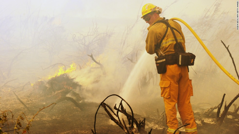 A firefighter goes after on a flareup along the Pacific Coast Highway near Point Mugu, California, on May 3.