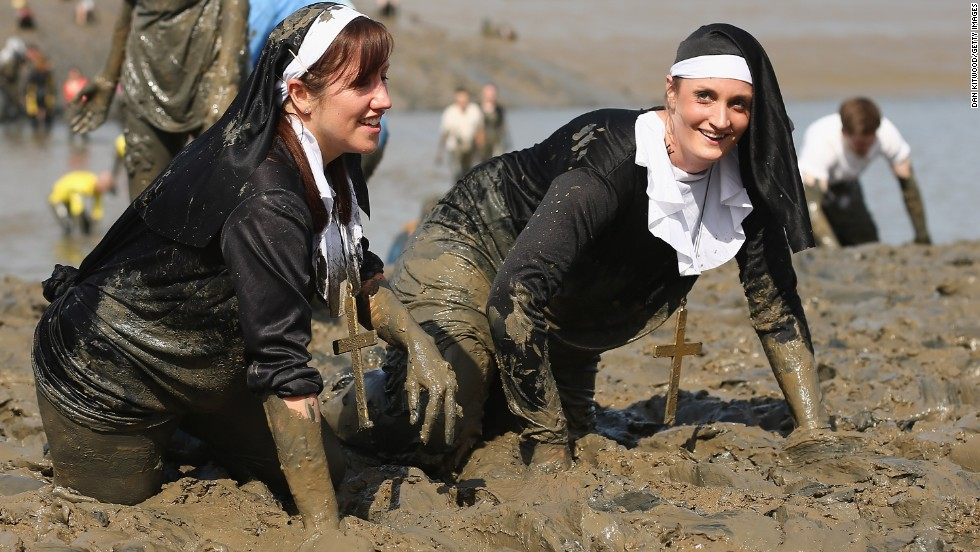 Competitors dressed as nuns crawl through the mud.