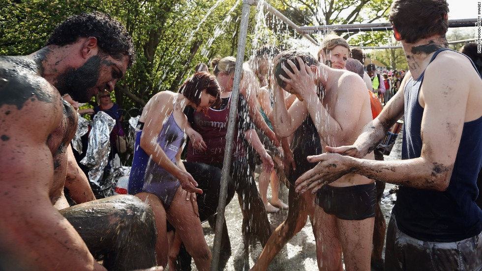 Participants shower off the mud after taking part in the race.