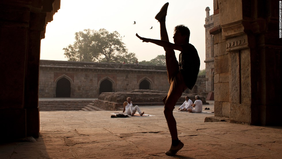 "MAY 07 - NEW DELHI, INDIA: Om Dubey, 20, shows off his moves as elderly yoga practitioners sit in the courtyard of a mosque. India's under-30s, comprising 60% of its 1.2 billion population, represent what experts call the ""demographic dividend"" of young workers that can help power the economy."