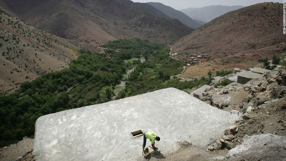 A man works on the roof of a traditional Berber house in Tisgui Ntknt on July 25, 2007. The village sits high in the Atlas Mountains of Morocco.