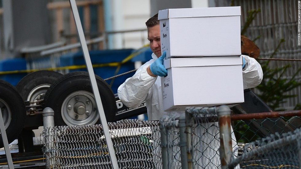 An FBI forensics team member removes evidence from the house.